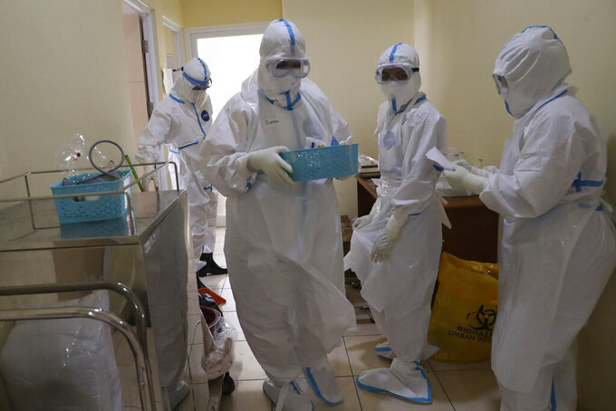 Health workers prepare to treat a COVID-19 patient at the Dr. Suyoto General Hospital in Jakarta, Indonesia, on July 29, 2021. As coronavirus cases skyrocket and deaths climb in Indonesia, health care workers are being depleted as the virus spares nobody. (AP Photo/Tatan Syuflana)