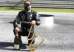 Mercedes driver Valtteri Bottas of Finland poses with his trophy and a bottle of champagne after winning the Austrian Formula One Grand Prix at the Red Bull Ring racetrack in Spielberg, Austria, Sunday, July 5, 2020. (Mark Thompson/Pool via AP)