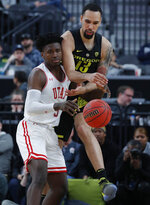 Utah's Donnie Tillman, left, and Oregon's Paul White vie for a rebound during the second half of an NCAA college basketball game in the quarterfinals of the Pac-12 men's tournament Thursday, March 14, 2019, in Las Vegas. (AP Photo/John Locher)