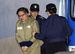 Former senior presidential aide Ahn Jong-beom, left, who faces six charges including abuse of power, arrives at the Seoul Central District Court in Seoul, South Korea, Tuesday, Feb. 13, 2018. A South Korean court is set to deliver a verdict Tuesday in the case of a woman at the center of an influence-peddling scandal that triggered the country's first presidential impeachment and the conviction of an heir to the Samsung empire. The Seoul Central District Court is also due to rule Tuesday on Ahn and Lotte Chairman Shin Dong-bin, who was charged with bribery. (AP Photo/Ahn Young-joon)