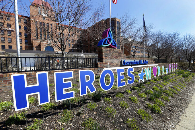 """A Heroes Work Here sign is shown outside Ascension St. John Hospital in Detroit, Thursday, April 2, 2020. Gov. Gretchen Whitmer said Thursday that Michigan is probably a month away from reaching the apex of the coronavirus COVID-19 outbreak. """"No one is immune from this virus,"""" she said during a news conference at the Capitol. (AP Photo/Paul Sancya)"""