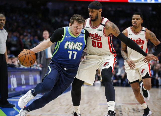 Dallas Mavericks forward Luka Doncic (77) drives as Portland Trail Blazers forward Carmelo Anthony (00) defends during the first half of an NBA basketball game Friday, Jan. 17, 2020, in Dallas. (AP Photo/Brandon Wade)