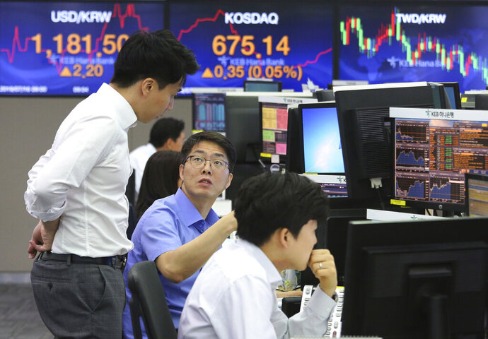 Currency traders work at the foreign exchange dealing room of the KEB Hana Bank headquarters in Seoul, South Korea, Tuesday, July 16, 2019. Asian shares were little changed and mixed in quiet trading Tuesday amid a lack of fresh market-moving news as investors looked ahead to earnings season. (AP Photo/Ahn Young-joon)