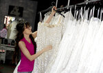 In this Friday, June 21, 2019, photo Assistant manager Brooke Hernandez hangs wedding gowns Friday, June 21, 2019 at Strut Bridal Shop in Tempe, Ariz. Cut-rate prices on websites that sell wedding dresses direct from China put pressure on owner Ann Campeau, who owns four bridal shops in California and Arizona. She has had customers come in after seeing low-end gowns online and expecting to get a dress at a similar price. (AP Photo/Matt York)