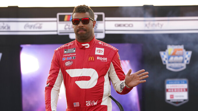 Bubba Wallace waves to the crowd during driver introductions prior to the start of the NASCAR Cup series auto race in Richmond, Va., Saturday, Sept. 11, 2021. (AP Photo/Steve Helber)