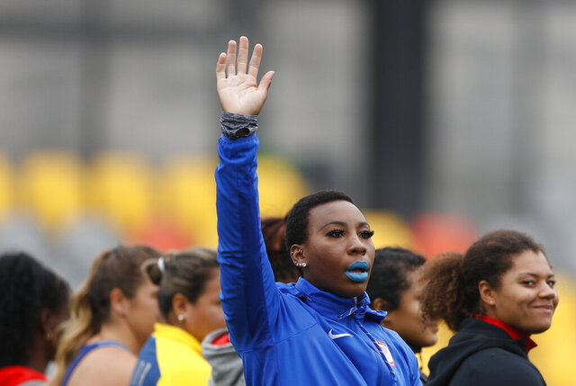 FILE - In this Aug. 10, 2019, file photo, Gwen Berry of the United States waves as she is introduced at the start of the women's hammer throw final during athletics competition at the Pan American Games in Lima, Peru. In the summer of 2019, U.S Olympic and Paralympic Committee CEO Sarah Hirshland reprimanded Berry and fencer Race Imboden for violating Rule 50, which prohibits inside-the-lines protests at the games, after Berry raised her fist and Imboden kneeled on the medals stand at the Pan-Am Games in Peru. (AP Photo/Rebecca Blackwell, File)