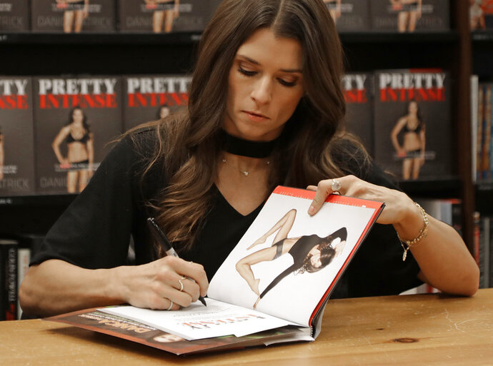 Danica Patrick autographs her new book during a book signing in Charlotte, N.C, Thursday, Jan. 4, 2018.  Patrick is back to work after a short offseason. The transition from race car driver to businesswoman was swift, and Patrick is now adjusting to a new celebrity life that doesn't include driving cars. (AP Photo/Chuck Burton)
