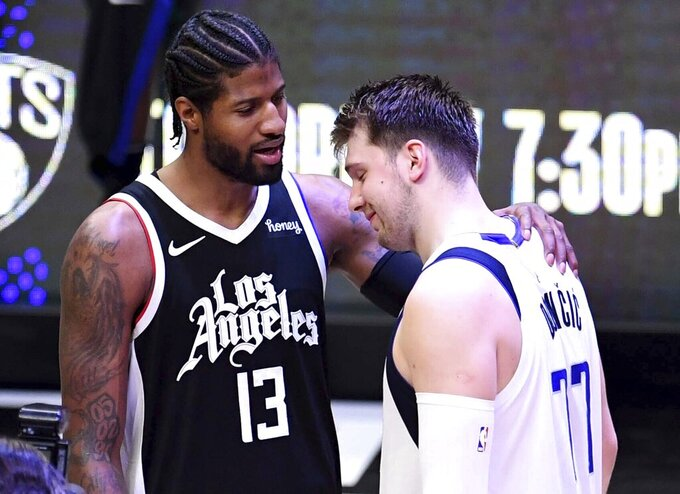 Los Angeles Clippers' Paul George (13) consoles Dallas Mavericks' Luka Doncic (77) after defeating the Mavericks during Game 7 of an NBA basketball first-round playoff series Sunday, June 6, 2021, in Los Angeles, Calif. (Keith Birmingham/The Orange County Register via AP)