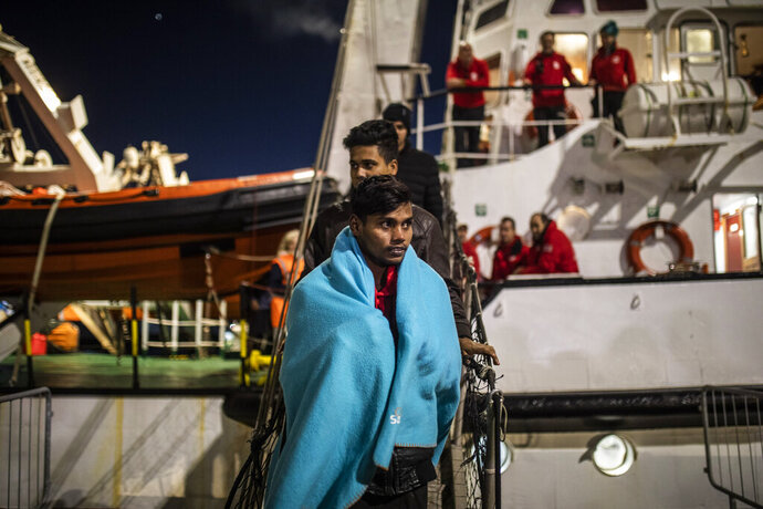 FILE - In this Jan. 15, 2020 file photo, men from Bangladesh disembark from the Open Arms rescue vessel at the port of Messina after being rescued on Friday off the Libyan coast, in Sicily, Italy. The European Union announced Tuesday, March 31, 2020 the launch of a new naval mission in the Mediterranean Sea aimed at enforcing the U.N arms embargo on Libya, after Italy blocked a previous operation claiming that the warships attracted migrants. (AP Photo/Santi Palacios, File)