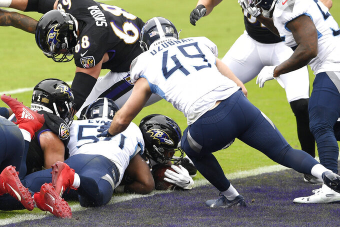 Baltimore Ravens running back J.K. Dobbins, center bottom, dives over the goal line while scoring a run against the Tennessee Titans during the first half of an NFL football game, Sunday, Nov. 22, 2020, in Baltimore. (AP Photo/Nick Wass)