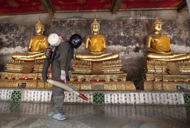 A worker sprays disinfectant at the base of Buddha statues as a precaution against the new coronavirus at Wat Suthat temple in Bangkok, Thailand, Tuesday, March 17, 2020. For most people, the new coronavirus causes only mild or moderate symptoms. For some it can cause more severe illness. (AP Photo/Sakchai Lalit)