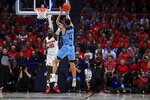 Dayton's Jalen Crutcher defends a shot by Rhode Island's Tyrese Martin during the first half of an NCAA college basketball game, Tuesday, Feb. 11, 2020, in Dayton, Ohio. (AP Photo/Aaron Doster)