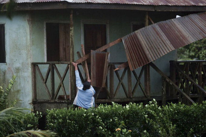 A woman works to recover the part of roof damaged by Hurricane Eta in Wawa, Nicaragua, Tuesday, Nov. 3, 2020. Eta slammed into Nicaragua's Caribbean coast with potentially devastating winds Tuesday, while heavy rains thrown off by the Category 4 storm already were causing rivers to overflow across Central America. (AP Photo/Carlos Herrera)
