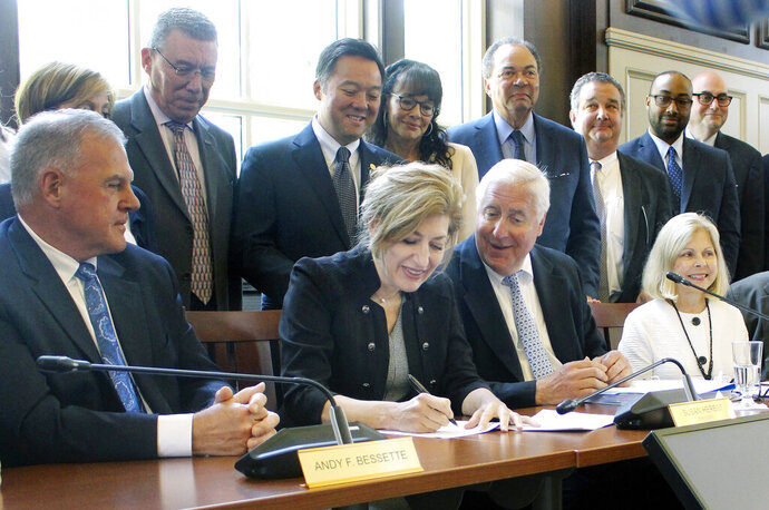 University of Connecticut President Susan Herbst, seated center, signs a contract on Wednesday, June 26, 2019, on the school's campus in Storrs, Conn., to move most of the schools athletic teams from the American Athletic Conference to the Big East. (AP Photo/Pat Eaton-Robb)