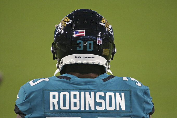 Jacksonville Jaguars running back James Robinson takes the field for warmups with the phrase Black Lives Matter on the back of his helmet before an NFL football game against the Miami Dolphins, Thursday, Sept. 24, 2020, in Jacksonville, Fla. (AP Photo/Stephen B. Morton)