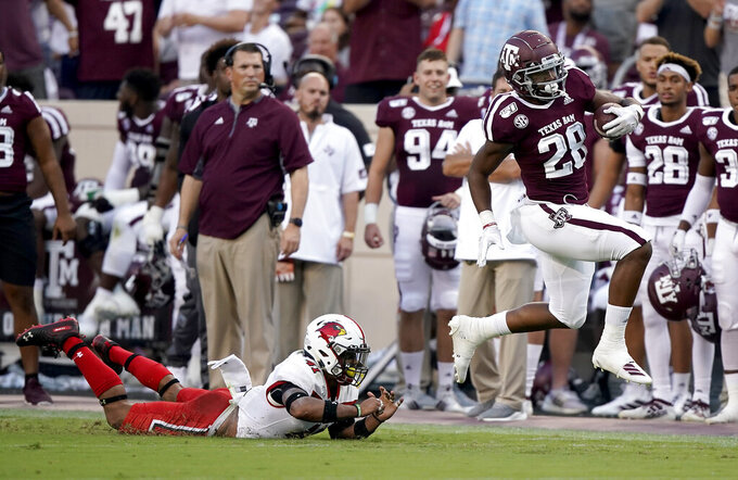 Texas A&M running back Isaiah Spiller (28) is tripped up by Lamar defensive back Michael Lawson (41) after a first down run during the first half of an NCAA college football game, Saturday, Sept. 14, 2019, in College Station, Texas. (AP Photo/Sam Craft)