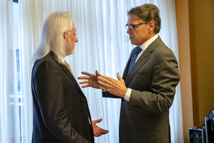 In this Nov. 12, 2018, photo provided by the U.S. Embassy in Kyiv, Energy Secretary Rick Perry talks with Michael Bleyzer during a speech in Kyiv, Ukraine. Bleyzer and Alex Cranberg, two political supporters of Perry secured a potentially lucrative oil-and-gas exploration deal from the Ukrainian government soon after Perry proposed one of the men as an adviser to the country's new president. (U.S. Embassy Kyiv via AP)