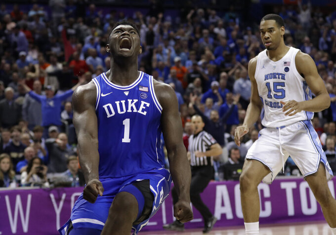 Duke's Zion Williamson (1) reacts after a dunk as North Carolina's Garrison Brooks (15) looks on during the second half of an NCAA college basketball game in the Atlantic Coast Conference tournament in Charlotte, N.C., Friday, March 15, 2019. (AP Photo/Nell Redmond)