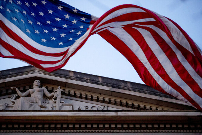 FILE - In this March 22, 2019 file photo, an American flag flies outside the Department of Justice in Washington.  The Justice Department has seized millions of dollars from cryptocurrency accounts that militant organization abroad, including al-Qaida and the Islamic State group, relied on to raise money for their operations, officials announced Thursday.  (AP Photo/Andrew Harnik)
