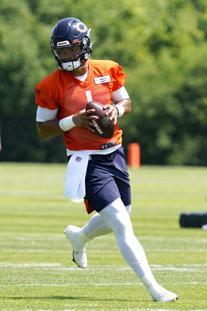Chicago Bears quarterback Justin Fields runs with a ball during NFL football practice in Lake Forest, Ill., Wednesday, June 9, 2021. (AP Photo/Nam Y. Huh)