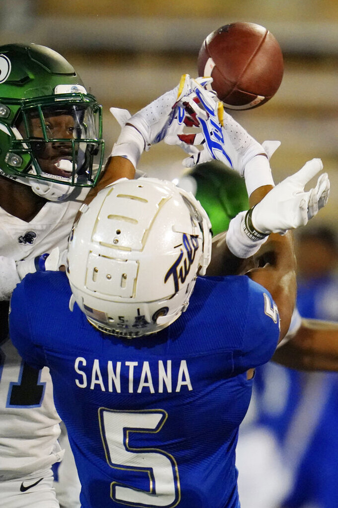 Tulane safety Larry Brooks, left, breaks up a pass intended for Tulsa wide receiver JuanCarlos Santana (5) during the second half of an NCAA college football game in Tulsa, Okla., Thursday, Nov. 19, 2020. (AP Photo/Sue Ogrocki)