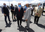 Denver Mayor Michael Hancock, right confers with Colorado Gov. Jared Polis as they tour the City and County of Denver's drive-up, COVID-19 test site in the parking lot of a downtown sports venue in an effort to stop the rise of the new coronavirus Thursday, May 21, 2020, in Denver. The free testing will be available daily for people who show symptoms of the coronavirus. City officials expect to administer more than 500 tests per day at the site, which opens Friday near the Pepsi Center. (AP Photo/David Zalubowski)