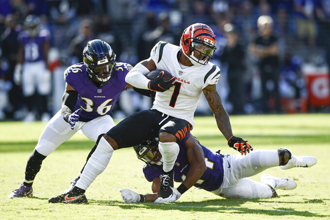 Baltimore Ravens safety Chuck Clark (36) and cornerback Marlon Humphrey (44) miss a tackle of Cincinnati Bengals wide receiver Ja'Marr Chase (1) before he took off for a long touchdown on a reception during the second half of an NFL football game, Sunday, Oct. 24, 2021, in Baltimore. (AP Photo/Gail Burton)
