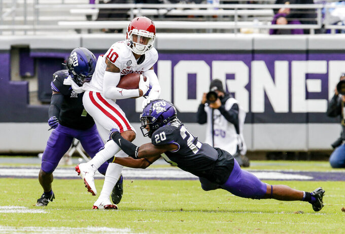 TCU cornerback Tre'Vius Hodges-Tomlinson (1) and safety La'Kendrick Van Zandt (20) tackle Oklahoma wide receiver Theo Wease (10) during the second half of an NCAA college football game, Saturday, Oct. 24, 2020, in Fort Worth, Texas.  (AP Photo/Brandon Wade)