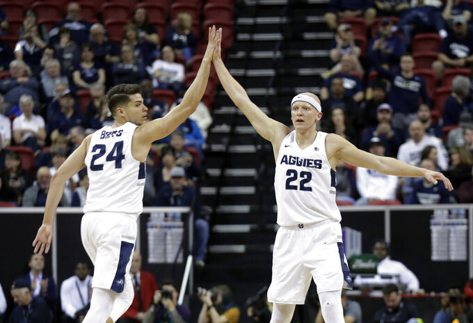 Utah State's Diogo Brito (24) congratulates Brock Miller (22) after a score during the first half of the team's NCAA college basketball game against Fresno State in the Mountain West Conference men's tournament Friday, March 15, 2019, in Las Vegas. (AP Photo/Isaac Brekken)