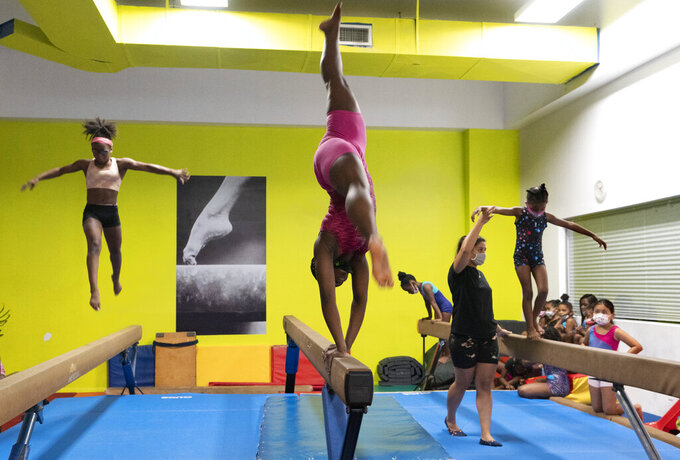 Alema Roberts, 13, center, trains on the balance beam, Thursday, July 22, 2021, at Power Moves Gymnastics and Fitness in Cedarhurst, N.Y. The face of gymnastics in the United States is changing. There are more athletes of color starting — and sticking — in a sport long dominated by white athletes at the highest levels. (AP Photo/Mark Lennihan)