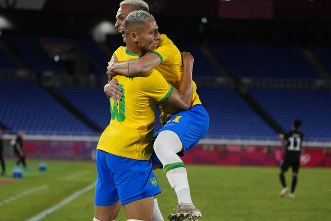 Brazil's Richarlison is embraced by a teammate after scoring his side's opening goal against Germany during a men's soccer match at the 2020 Summer Olympics, Thursday, July 22, 2021, in Yokohama, Japan. (AP Photo/Kiichiro Sato)