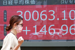 A woman walks by an electronic stock board of a securities firm in Tokyo, Wednesday, Sept. 8, 2021. Stocks were mixed in Asia on Wednesday after Wall Street closed mostly lower as traders returned from the Labor Day holiday. (AP Photo/Koji Sasahara)
