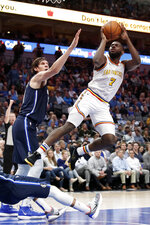 Golden State Warriors forward Eric Paschall (7) goes up for a shot over Dallas Mavericks' Boban Marjanovic, left, and Jalen Brunson, bottom, in the first half of an NBA basketball game in Dallas, Wednesday, Nov. 20, 2019. (AP Photo/Tony Gutierrez)
