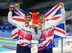 """FILE - In this July 26, 2021, file photo, Thomas Daley and Matty Lee, of Britain, pose for a photo after winning gold medals during the men's synchronized 10-meter platform diving final at the Tokyo Aquatics Centre at the 2020 Summer Olympics in Tokyo, Japan. The Tokyo Games are shaping up as a watershed for LGBTQ Olympians. Daley announced in 2013 that he was dating a man and """"couldn't be happier,"""" his coming out was an act of courage that, with its rarity, also exposed how the top echelons of sport weren't seen as a safe space by the vast majority of LGBTQ athletes. (AP Photo/Dmitri Lovetsky, File)"""