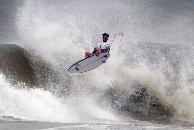 Brazil's Gabriel Medina goes to the air during the quarterfinals of the men's surfing competition at the 2020 Summer Olympics, Tuesday, July 27, 2021, at Tsurigasaki beach in Ichinomiya, Japan. (AP Photo/Francisco Seco)