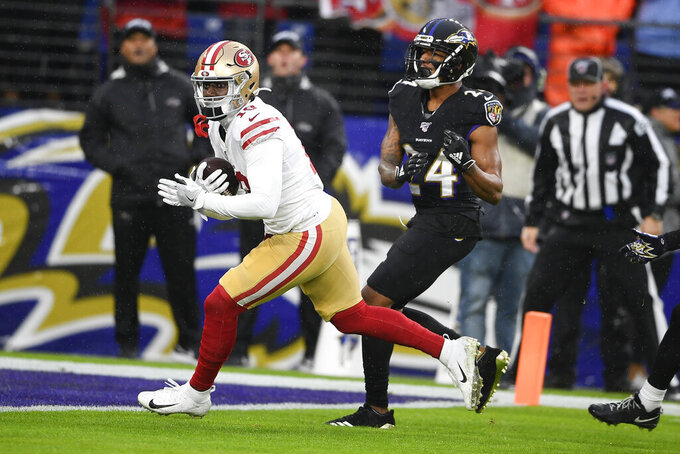 San Francisco 49ers wide receiver Deebo Samuel (19) rans past Baltimore Ravens cornerback Marcus Peters (24) to score a touchdown in the first half of an NFL football game, Sunday, Dec. 1, 2019, in Baltimore, Md. (AP Photo/Nick Wass)
