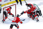 Chicago Blackhawks' Calvin de Haan (44) clears the pucks from the crease as goaltender Corey Crawford and Brent Seabrook (7) defend against Dallas Stars' Jason Dickinson during the second period of an NHL hockey game Tuesday, Nov. 26, 2019, in Chicago. (AP Photo/Charles Rex Arbogast)