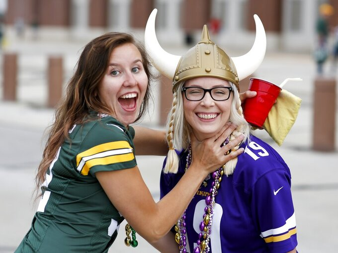 Green Bay Packers fan Courtney Ashwell and Minnesota Vikings Chelsea Ashwell have some fun outside Lambeau Field before an NFL football game Sunday, Sept. 15, 2019, in Green Bay, Wis. (AP Photo/Matt Ludtke)