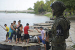 A Mexican marine stands guard on the Suchiate River, watching out for migrants crossing from Guatemala to Ciudad Hidalgo, as locals stand on a raft in Mexico, Sunday, June 16, 2019. Mexico faces heightened pressure from the U.S. to reduce the surge of mostly Central American migrants through its territory. (AP Photo/Idalia Rie)
