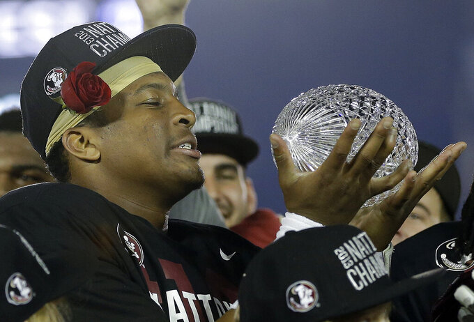 FILE - In this Jan. 6, 2014, file photo, Florida State's Jameis Winston holds The Coaches' Trophy after the NCAA BCS National Championship college football game against Auburn, in Pasadena, Calif. Florida State won 34-31. (AP Photo/David J. Phillip, File)