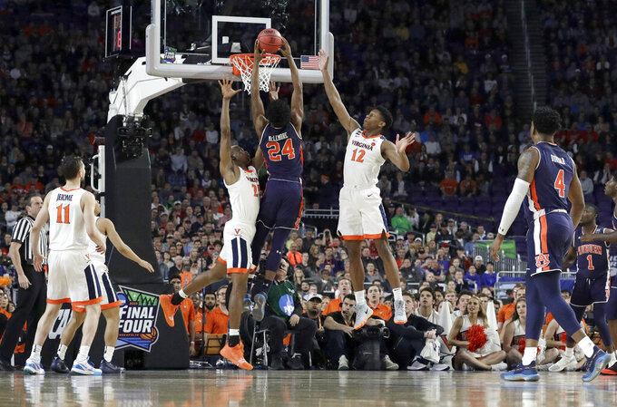 Auburn's Anfernee McLemore (24) goes up for a basket against Virginia's Mamadi Diakite (25) and De'Andre Hunter (12) during the first half in the semifinals of the Final Four NCAA college basketball tournament, Saturday, April 6, 2019, in Minneapolis. (AP Photo/David J. Phillip)