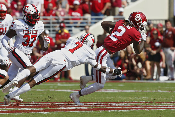 Oklahoma wide receiver CeeDee Lamb (2) avoids a tackle by Texas Tech defensive back Adrian Frye (7) in the second quarter of an NCAA college football game in Norman, Okla., Saturday, Sept. 28, 2019. (AP Photo/Sue Ogrocki)