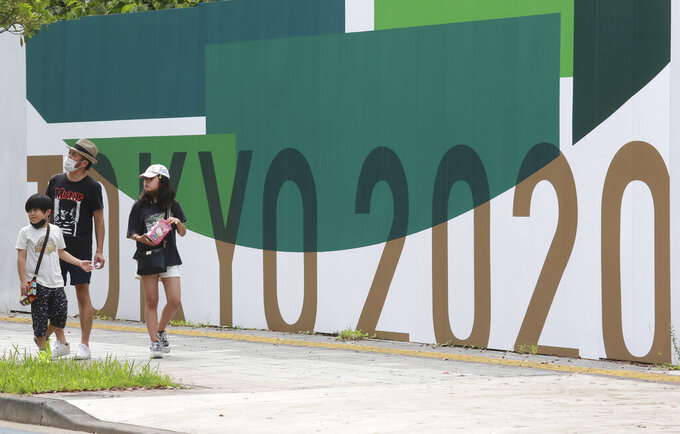 People walk by posters to promote Tokyo 2020 Olympics in Tokyo, Wednesday, July 14, 2021. The Olympic Games are scheduled to begin on July 23. (AP Photo/Koji Sasahara)