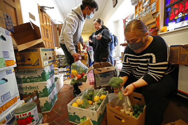 FILE - In this Tuesday, May 12, 2020 file photo, Laura Porras, right, prepares bags of fresh vegetables as Justin Ruiz, 17, left, and Porras' niece Ana Karen Porras, 14, help in the vestibule at Lutheran Church of the Good Shepherd in the Bay Ridge neighborhood of the Brooklyn borough of New York. The effort, which started two months earlier, is coordinated by the Brooklyn Immigrant Community Support mutual aid group who saw a need for emergency food aid for undocumented immigrants, who couldn't apply for or receive government assistance in the wake of shutdowns caused by concerns over the spread of the new coronavirus. (AP Photo/Kathy Willens)