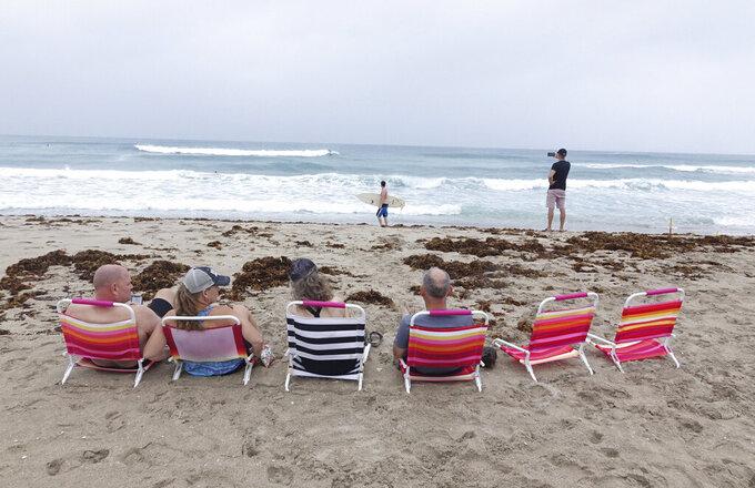 Spectators watch surfers in Delray Beach, Sunday, Aug. 2, 2020, as Tropical Storm Isaias brushes past the East Coast of Florida. (Joe Cavaretta/South Florida Sun-Sentinel via AP)