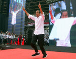 FILE - In this April 13, 2019, photo, Indonesian presidential candidate Joko Widodo, center, during a campaign rally at Gelora Bung Karno Stadium in Jakarta, Indonesia. Nearly 193 million Indonesians are eligible to vote in presidential and legislative elections on Wednesday. President Joko Widodo, the first Indonesian president from outside the Jakarta elite, is competing against Prabowo Subianto, a former special forces general from the era of authoritarian rule under military dictator Suharto.(AP Photo/Achmad Ibrahim, File)