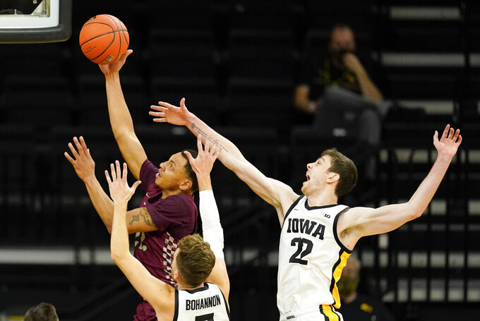 North Carolina Central guard C.J. Keyser, left, drives to the basket ahead of Iowa guard Jordan Bohannon and forward Patrick McCaffery (22) during the first half of an NCAA college basketball game, Wednesday, Nov. 25, 2020, in Iowa City, Iowa. (AP Photo/Charlie Neibergall)
