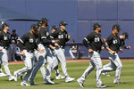 Chicago White Sox players warm up before a spring training baseball game against the Milwaukee Brewers, Wednesday, March 4, 2020, in Phoenix, Ariz. (AP Photo/Sue Ogrocki)