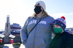 Kelly Roccabello and her son, Giovanni, 6, speak to a reporter outside the pro shop at Gillette Stadium, Monday Jan. 25, 2021, in Foxborough, Mass. Tom Brady is going to the Super Bowl for the 10th time, and New England Patriots football fans are cheering for him -- just like before. (AP Photo/Elise Amendola)
