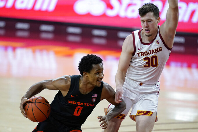 Southern California guard Noah Baumann (30) defends against Oregon State guard Gianni Hunt (0) during the first half of an NCAA college basketball game Thursday, Jan. 28, 2021, in Los Angeles. (AP Photo/Ashley Landis)
